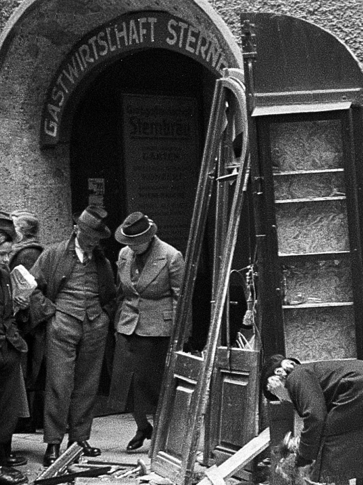 Therese Spiegel cleaning up in front of her shop after it had been plundered by Nazi Storm-troopers and SS men in the »Reichskristallnacht« pogrom<br>
